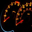 Backlit car dashboard dials glowing at night — Stock Photo