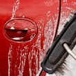 Постер, плакат: Cleaning the car with a brush