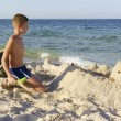 A boy playing in the sand on the beach — Stock Photo