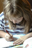 Girl writes homework — Stock Photo