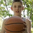 Stock Photo: Young boy holding basketball in his hand