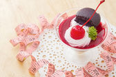 Cherry cheesecake with macaron and measurements tape — Stock Photo