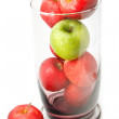 Green apple on red apple in glass jar — Stock Photo
