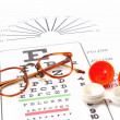 eye test chart and glasses and containers for contact lenses  — Stock Photo