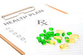 Pill capsules resting on medical health plan or patient record f — Stock Photo
