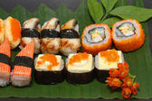 Traditional Japanese food Sushi on black plate — Stock Photo