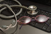 Stethoscope and glasses rest on keyboard notebooks — Stock Photo