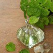 Essential aroma peppermint oil and fresh mint on wooden background — Stock Photo
