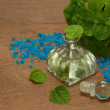 Essential aroma peppermint oil and fresh mint on wooden backgr — Stock Photo