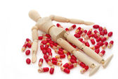 Drewniany model manekina, leżącego nad kupie tabletki — Zdjęcie stockowe