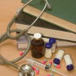 Stethoscope and  medications on  medical book — Stock Photo