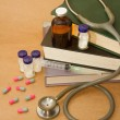 Stock Photo: Stethoscope and medications on medical book