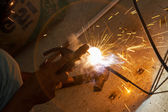 Worker un protective gloves welding metal and sparks, poor safet — Stock Photo