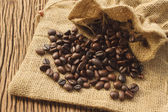 Coffee beans in coffee bag on wooden background — Stock Photo