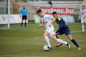 KAPOSVAR, HUNGARY - MARCH 16: Kink Tarmo (white 9) in action at a Hungarian Championship soccer game - Kaposvar (white) vs Puskas Akademia (blue) on March 16, 2014 in Kaposvar, Hungary. — Photo