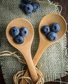 Arándanos en una cuchara con el fondo de arpillera tejida — Foto de Stock