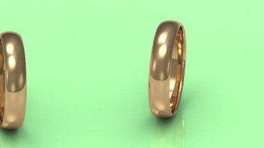 Rotating gold wedding rings on a green background — Stock Video