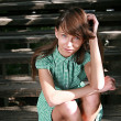 Young pretty thoughtful girl sitting on wooden stairs - Stock Photo