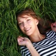 Stock Photo: Smiling girl laying on grass