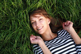 Smiling girl laying on grass — Stock Photo