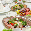Foto de Stock  : Elegant table setting in restaurant with dishes full of food for celebration