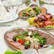 Stockfoto: Elegant table setting in restaurant with dishes full of food for celebration