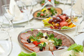 Elegant table setting in restaurant with dishes full of food for celebration — Stock Photo
