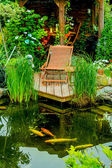 Charming sitting place at garden pond — Stock Photo