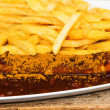 The currywurst with sauce and frites — Stock Photo
