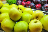 Yellow apples and violet nectarines — Stock Photo