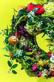 Wreath of flowers on yellow background — Stock Photo