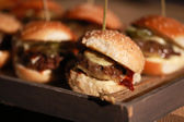 Hamburger sliders on a rustic cutting wooden board. — Stock Photo