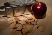Smiley Metal grater and apple on cutting board — Stock Photo