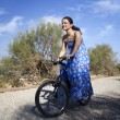 Pretty young woman riding bike in a country road — Stock Photo #12747232