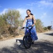 Pretty young woman riding bike in a country road — Stock Photo