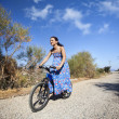 Pretty young woman riding bike in a country road — Stock Photo #12747343