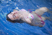 Attractive young woman floating in a swimming pool — Stock Photo