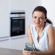 Portrait of a happy female holding a glass in the kitchen — Stock Photo #13060199