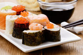 Mixed sushi on a white plate with soy sauce wasabi and ginger — Stock Photo