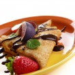 Strawberry crepes with chocolate syrup and figs over white close — Stock Photo