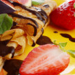 Strawberry crepes with chocolate syrup and figs over white — Stock Photo