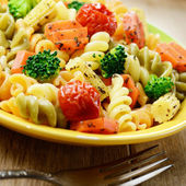 Pasta fusilli salad with broccoli, carrot, corn, and tomatoes on — Stock Photo