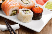 Mixed sushi set on a white plate — Stock Photo