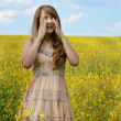 Stock Photo: Young womsneezing at canolfield