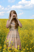 Young woman sneezing at canola field — Stock Photo