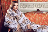 Fashion model posing in a fur coat — Stock Photo