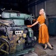 Fashion girl working on the industrial machine at the factory — Stock Photo