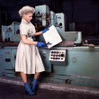Stock Photo: Fashion girl working on the industrial machine at the factory