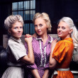 Three fashion girls by the industrial machine at the factory - Stockfoto