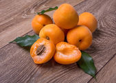 Apricots with leaves on the textured wooden table. — Stock Photo